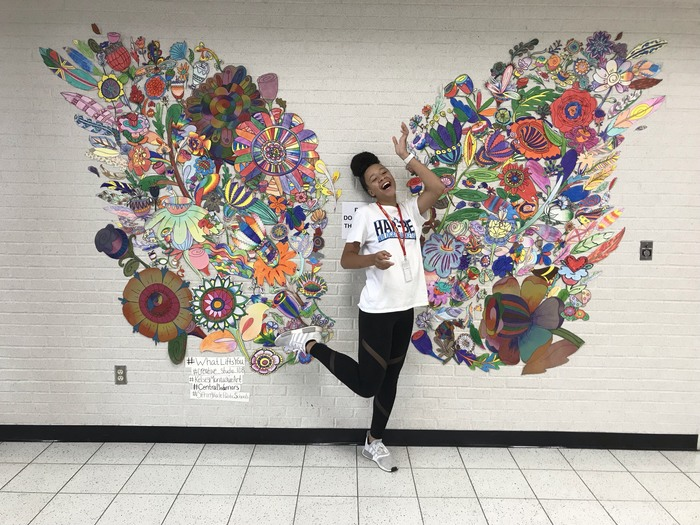 student in front of mural