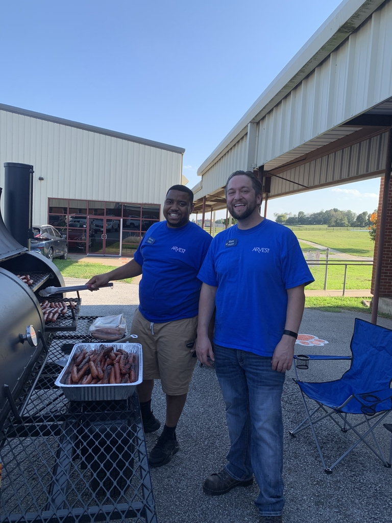 Arvest Bank volunteers cooking hotdogs.